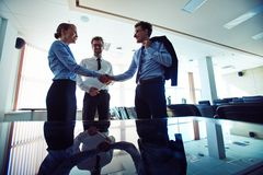 Business agreement. Two partners handshaking after signing agreement in office Stock Photos