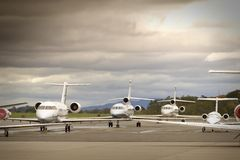 Business Aircraft. Corporate aircraft sit on a ramp at an airport under cloudy skies royalty free stock images