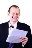 Business amusement. A businessman laughing as he reads a letter and find the content amusing, isolated on white Stock Images
