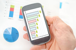 Business analysis concept on a smartphone. Held by a hand Stock Image