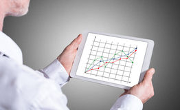 Business analysis concept on a tablet. Man holding a tablet showing business analysis concept Stock Photos