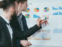 Business analysis report corporate meeting. Business analysis report. Corporate meeting. Colleagues reviewing graphs on whiteboard royalty free stock photo