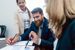 Business analyst smiling while interpreting financial reports sh. Owing profit and development during meeting with his female colleagues in the office royalty free stock image