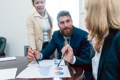 Business analyst smiling while interpreting financial reports sh. Owing profit and development during meeting with his female colleagues in the office stock photography