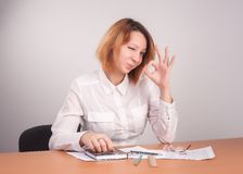 Business analyst woman winks and shows sign ok. Caucasian businesswoman sitting at desk in casual clothes. She is analyzes sales statistics, winks and shows ok royalty free stock images