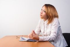 Business analyst woman working. Caucasian businesswoman sitting at desk in casual clothes and analyzing sales statistics royalty free stock photo