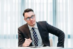 Business analyst work corporate manager office. Business analyst at work. successful corporate manager. young handsome stylish man in glasses sitting in office royalty free stock image