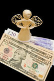Business Angel. A raffia angel standing on a pile of ten dollar bills and twenty pound notes set against a black background Stock Image