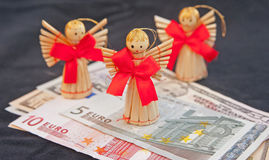 Business Angels in Europe. Business angels on top of Euro and Dollar bills metaphor for investments in start-up companies Royalty Free Stock Photography