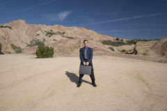 Business anywhere. Man standing in the desert with his briefcase Stock Photos