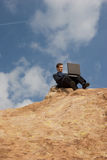 Business anywhere. Man sitting in the desert with his brief case Stock Image