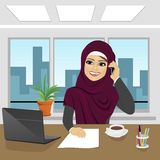 Business arab woman with laptop at office wearing hijab talking on phone Royalty Free Stock Images