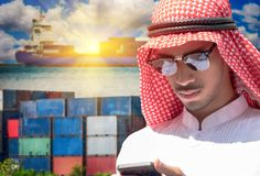 Business arabian man using smartphone for business industry. On logistics and transportation of Container Cargo ship background Stock Images