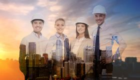 Business team in white hard hats. Business, architecture and building concept - happy team of architects in white hard hats over city background with double Stock Photos