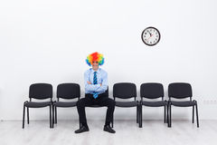 Business as unusual. Businessman with clown hair sitting on row of chairs Royalty Free Stock Photography