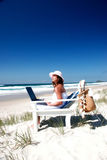 Business as usual. Woman sitting in beach chair with laptop best of both worlds Royalty Free Stock Images