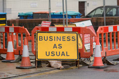 Business as Usual sign in town centre. Next to are fenced off from people Stock Photography