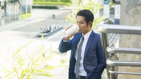 Business asia man stand with paper cup of drink at outdoor pedes Stock Photo