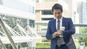 Business asia man stand with paper cup of drink at outdoor pedes Stock Images