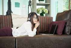 Business Asian girl leaning and using a laptop on sofa, person stock image