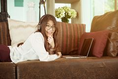 Business Asian girl leaning and using a laptop on sofa, person stock images