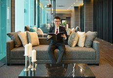 Business Asian man reading a book on sofa in luxury condo Stock Images