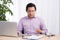 Business asian man sitting at his desk working on a computer and. Looking concentrated royalty free stock photos