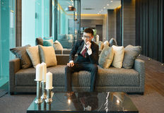 Business Asian man is stressed out and nervous, thinking on sofa. In luxury condo Royalty Free Stock Image