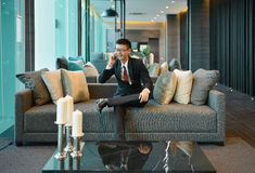 Business Asian man using a smartphone on sofa in luxury condo stock image