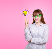 Business Asian woman with green glasses stand and have idea lamp. Bulb light on woman fingertip pink background, for your design for poster and advertising text Royalty Free Stock Images