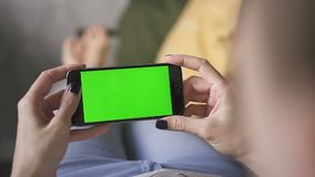 Business asian woman holding a online mockup green screen phone, on couch at home stock video