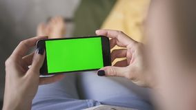 Business asian woman lying on the couch at home, holding a mockup green screen phone stock footage