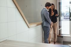 Business associates discussing work in office stairway. Two business colleagues standing in office stairway and looking at mobile phone. Male and female business Royalty Free Stock Photography