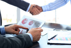 Business associates shaking hands in office. Business person analyzing financial statistics displayed on the tablet screen Stock Image