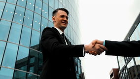 Business associates shaking hands. Slow motion. Businessman partners shaking hands beginning their partnership with modern glass building at the background. Teal stock video