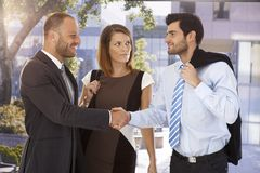 Business associates shaking hands on the street. In front of bank center building Stock Photo