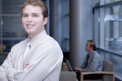 Business Assurance. Young businessman smiles with assurance. Office background with employee at keyboard Stock Photo
