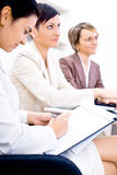 Business Attendees. Three businesswoman attending on business training. Sitting in a row, making notes, smiling Royalty Free Stock Images