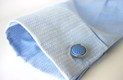Business Attire. Blue business shirt cuff and round silver cufflink with blue material insert Royalty Free Stock Photography