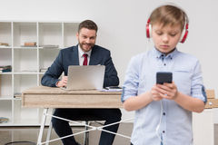 Business attire entrepreneur at office with his son listening music. In foreground Royalty Free Stock Photos