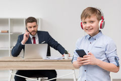 Business attire entrepreneur at office with his son listening music. In foreground Stock Images