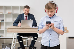 Business attire entrepreneur at office with his son listening music. In foreground Stock Photos