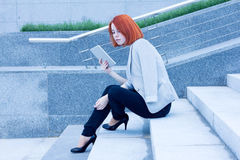 Business attractive woman sitting on the street with a tablet on a sunny day Royalty Free Stock Photo