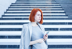 Business attractive woman with a tablet in hands looking aside on the background of the stairs in the business center Stock Photography