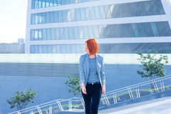Business attractive woman walking down the street on a background of a skyscraper Royalty Free Stock Photography