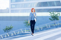 Business attractive women walking down the street on a background of a skyscraper Royalty Free Stock Photo