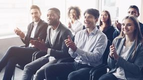 Business audience applauding to speaker at conference