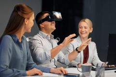 Developers with virtual reality headset at office. Business, augmented reality and technology concept - developers with singapore city on virtual headset or 3d Stock Photography