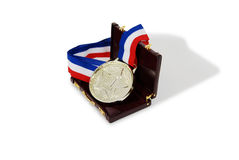 Business award. Award ribbon with gold medallion, burgandy leather Briefcase used to carry items to the office Stock Photos
