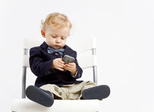 Business baby with phone. Baby dressed in business outfit texting on smart phone royalty free stock photography